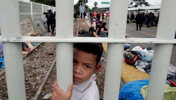 A Honduran migrant child part of a caravan trying to reach the US looks though the gate on the bridge that connects Mexico and Guatemala in Tecun Uman Guatemala